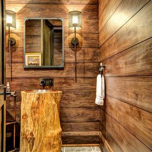 Cette photo montre un WC et toilettes montagne avec un carrelage gris, un mur marron, un sol en ardoise et un lavabo posé.