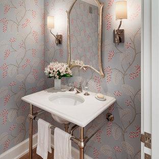 Inspiration pour un WC et toilettes traditionnel avec un mur gris, un sol en bois foncé, un lavabo encastré, un sol marron, un plan de toilette blanc et du papier peint.