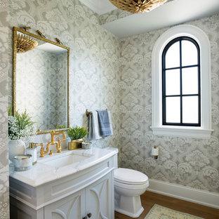 Идея дизайна: туалет в стиле современная классика с столешницей из искусственного кварца, фасадами с выступающей филенкой, белыми фасадами, разноцветными стенами, темным паркетным полом, врезной раковиной и коричневым полом