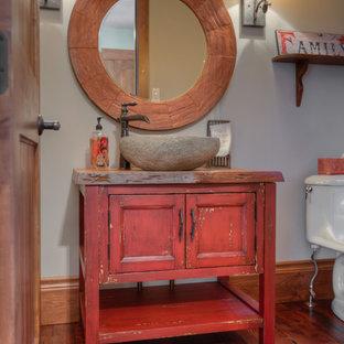 Ispirazione per un bagno di servizio rustico di medie dimensioni con consolle stile comò, ante rosse, WC a due pezzi, pareti grigie, pavimento in legno massello medio, lavabo a bacinella, pavimento marrone e top marrone