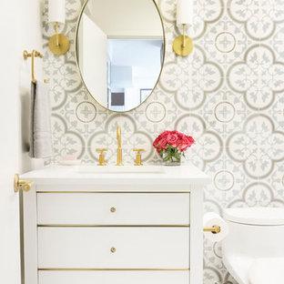 Cette image montre un petit WC et toilettes traditionnel avec un placard à porte plane, des portes de placard blanches, un WC à poser, un carrelage blanc, des carreaux de béton, un mur blanc, un sol en carrelage de porcelaine, un lavabo encastré, un plan de toilette en quartz modifié, un sol blanc et un plan de toilette blanc.