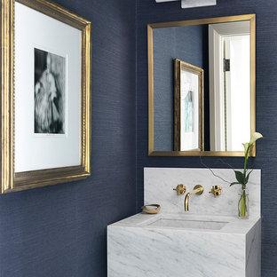 Inredning av ett modernt toalett, med blå väggar och ett väggmonterat handfat