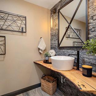 Inspiration pour un WC et toilettes chalet avec un placard sans porte, des portes de placard en bois brun, un carrelage gris, un carrelage de pierre, un mur beige, une vasque, un plan de toilette en bois, un sol gris et un plan de toilette marron.