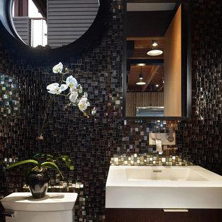 Новые идеи обустройства дома: маленький туалет в стиле модернизм с монолитной раковиной, плоскими фасадами, темными деревянными фасадами, раздельным унитазом, черной плиткой, стеклянной плиткой, черными стенами, бетонным полом, столешницей из искусственного камня, бежевым полом и белой столешницей