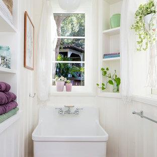 ロサンゼルスの小さい地中海スタイルのおしゃれなトイレ・洗面所 (テラコッタタイル、白い壁、セラミックタイルの床、壁付け型シンク、オープンシェルフ、白いキャビネット、茶色い床) の写真
