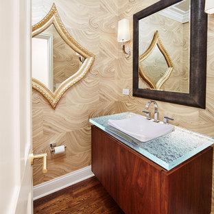 Idéer för funkis blått toaletter, med släta luckor, skåp i mellenmörkt trä, bänkskiva i glas, beige väggar, mellanmörkt trägolv och brunt golv