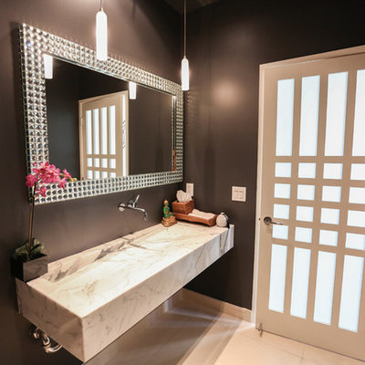 Example of a small minimalist marble floor powder room design in Los Angeles with black walls, marble countertops and a trough sink