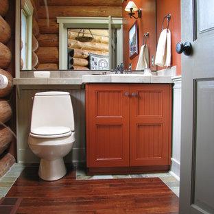 Diseño de aseo rústico, de tamaño medio, con armarios con paneles empotrados, puertas de armario naranjas, parades naranjas, suelo de madera en tonos medios y sanitario de dos piezas