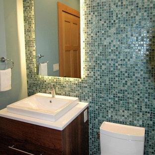 Свежая идея для дизайна: маленький туалет в стиле современная классика с фасадами островного типа, темными деревянными фасадами, унитазом-моноблоком, синей плиткой, стеклянной плиткой, зелеными стенами, паркетным полом среднего тона, столешницей из искусственного кварца, настольной раковиной и коричневым полом - отличное фото интерьера