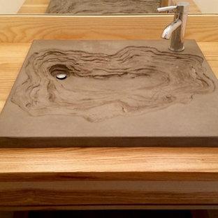 Réalisation d'un petit WC et toilettes chalet avec des portes de placard en bois clair, un mur blanc, une vasque et un plan de toilette en bois.