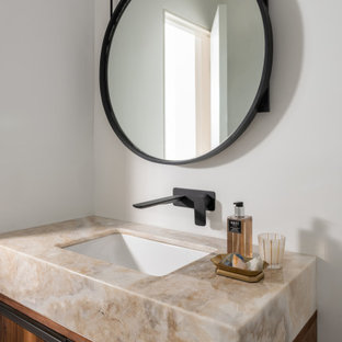 Powder room - small contemporary powder room idea in Dallas with flat-panel cabinets, medium tone wood cabinets, white walls, an undermount sink and beige countertops