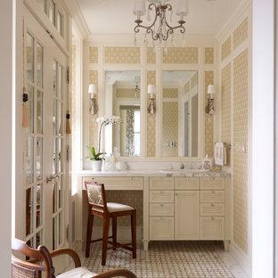 На фото: туалеты в классическом стиле с накладной раковиной, фасадами с выступающей филенкой, бежевыми фасадами, бежевой плиткой и белой столешницей