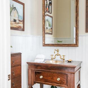 На фото: туалет среднего размера в классическом стиле с открытыми фасадами, темными деревянными фасадами, паркетным полом среднего тона, столешницей из дерева, бежевыми стенами, накладной раковиной, коричневым полом и коричневой столешницей с