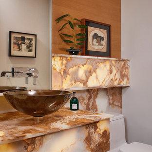 Стильный дизайн: туалет в стиле ретро с коричневыми стенами, настольной раковиной, столешницей из оникса и разноцветной столешницей - последний тренд