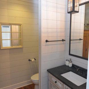 Cette image montre un très grand WC et toilettes rustique avec un placard en trompe-l'oeil, des portes de placard en bois vieilli, un WC à poser, un mur blanc, un sol en bois brun, un lavabo encastré et un plan de toilette en granite.