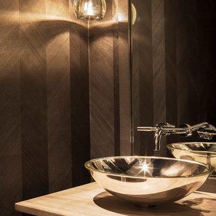 На фото: туалеты среднего размера в стиле модернизм с плоскими фасадами, серыми стенами, настольной раковиной, столешницей из дерева, темными деревянными фасадами и коричневой столешницей
