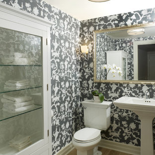 Photo of a mid-sized traditional powder room in Vancouver with a pedestal sink, white cabinets, a two-piece toilet and light hardwood floors.