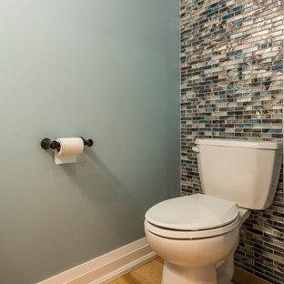 Idées déco pour un petit WC et toilettes contemporain avec un placard en trompe-l'oeil, des portes de placard blanches, un WC séparé, un carrelage bleu, des plaques de verre, un mur bleu, un sol en bois clair, un lavabo posé, un plan de toilette en quartz modifié, un sol beige et un plan de toilette gris.