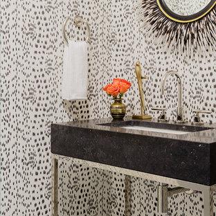 Idée de décoration pour un petit WC et toilettes design avec un WC à poser, un sol en marbre, un plan de toilette en marbre, un sol blanc, un mur multicolore, un lavabo encastré et un plan de toilette noir.