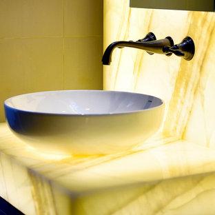 Стильный дизайн: туалет в стиле фьюжн с настольной раковиной, столешницей из оникса и желтой столешницей - последний тренд