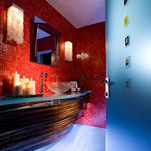 Esempio di un bagno di servizio contemporaneo di medie dimensioni con consolle stile comò, ante in legno bruno, WC monopezzo, piastrelle rosse, piastrelle di vetro, pareti rosse, pavimento in marmo, lavabo a bacinella, top in vetro e pavimento bianco