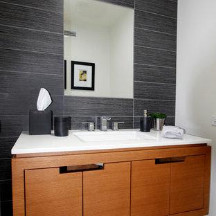 Diseño de aseo retro, de tamaño medio, con lavabo bajoencimera, armarios con paneles lisos, puertas de armario de madera oscura, baldosas y/o azulejos multicolor, encimera de cuarzo compacto, paredes negras y encimeras blancas