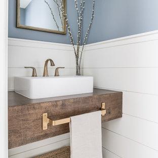 Неиссякаемый источник вдохновения для домашнего уюта: маленький туалет в морском стиле с синими стенами, столешницей из дерева, подвесной тумбой, стенами из вагонки, темными деревянными фасадами и настольной раковиной