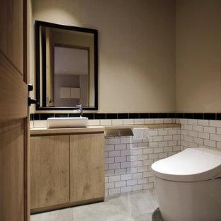 Стильный дизайн: маленький туалет в классическом стиле с фасадами островного типа, фасадами цвета дерева среднего тона, унитазом-моноблоком, белой плиткой, керамогранитной плиткой, белыми стенами, полом из ламината, настольной раковиной, столешницей из дерева, серым полом и бежевой столешницей - последний тренд