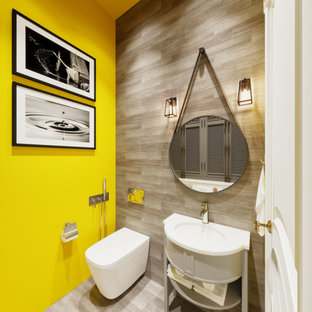 На фото: туалеты в современном стиле с фасадами островного типа, белыми фасадами, инсталляцией, серой плиткой, желтыми стенами, врезной раковиной, серым полом и белой столешницей
