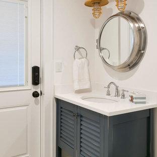 На фото: туалет в морском стиле с фасадами с филенкой типа жалюзи, синими фасадами, полом из цементной плитки, врезной раковиной, столешницей из искусственного кварца, разноцветным полом и белой столешницей с