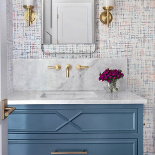 オースティンのトランジショナルスタイルのおしゃれなトイレ・洗面所 (落し込みパネル扉のキャビネット、青いキャビネット、マルチカラーのタイル、アンダーカウンター洗面器、白い洗面カウンター) の写真