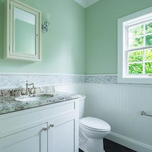 Klassisk inredning av ett mellanstort grå grått toalett, med luckor med infälld panel, vita skåp, en toalettstol med separat cisternkåpa, vit kakel, mosaik, gröna väggar, klinkergolv i porslin, ett undermonterad handfat, granitbänkskiva och svart golv