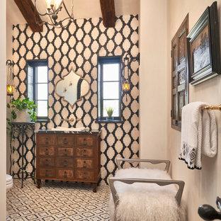 ウィチタのサンタフェスタイルのおしゃれなトイレ・洗面所 (フラットパネル扉のキャビネット、中間色木目調キャビネット、モノトーンのタイル、ベージュの壁、オーバーカウンターシンク、マルチカラーの床、黒い洗面カウンター、独立型洗面台、表し梁) の写真