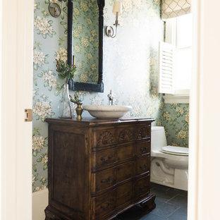 Modelo de aseo clásico con armarios tipo mueble, puertas de armario de madera oscura, sanitario de una pieza, paredes azules, suelo de pizarra, lavabo sobreencimera, encimera de madera y suelo gris