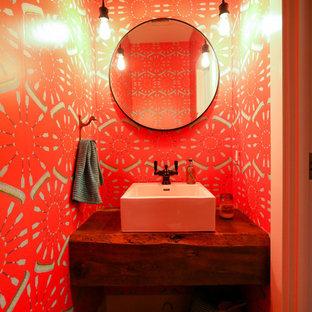 Aménagement d'un petit WC et toilettes classique avec un placard sans porte, des portes de placard en bois sombre, un WC séparé, un mur rouge, un sol en bois foncé, une vasque, un plan de toilette en bois, un sol marron et un plan de toilette marron.