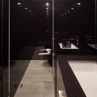 Idée de décoration pour un WC et toilettes design avec un placard à porte plane, des portes de placard blanches, un WC suspendu, un carrelage noir, des plaques de verre, un mur noir, un sol en carrelage de porcelaine, un lavabo encastré et un plan de toilette en granite.