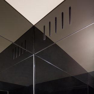 Réalisation d'un WC et toilettes design avec un placard à porte plane, des portes de placard blanches, un WC suspendu, un carrelage noir, des plaques de verre, un mur noir, un sol en carrelage de porcelaine, un lavabo encastré et un plan de toilette en granite.