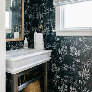 Inspiration for a coastal light wood floor and beige floor powder room remodel in Denver with black walls and a console sink