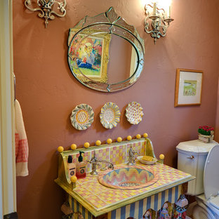 Design ideas for a medium sized bohemian cloakroom in Austin with light hardwood flooring, a built-in sink, tiled worktops, a two-piece toilet, multi-coloured tiles, pink walls and multi-coloured worktops.