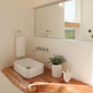 Foto de aseo contemporáneo, pequeño, con lavabo sobreencimera, encimera de madera, suelo de baldosas de cerámica y encimeras marrones