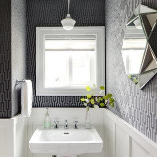Foto på ett litet vintage toalett, med ett piedestal handfat och flerfärgade väggar