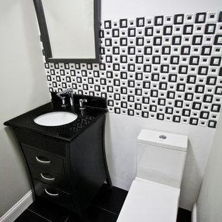 Exemple d'un petit WC et toilettes tendance avec un lavabo encastré, un placard avec porte à panneau encastré, des portes de placard noires, un plan de toilette en quartz modifié, un WC séparé, un carrelage noir et blanc, des carreaux de céramique, un mur vert, un sol en carrelage de céramique et un sol noir.