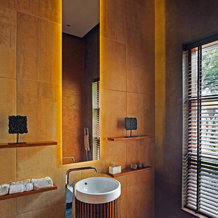 This is an example of a world-inspired cloakroom in Bengaluru with orange walls, a pedestal sink and grey floors.