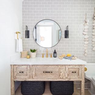 На фото: туалет в морском стиле с фасадами островного типа, светлыми деревянными фасадами, унитазом-моноблоком, серой плиткой, плиткой кабанчик, светлым паркетным полом, врезной раковиной, бежевым полом и белой столешницей с