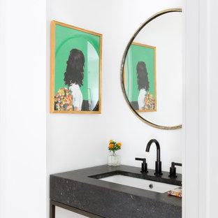 Cette photo montre un WC et toilettes scandinave de taille moyenne avec un placard en trompe-l'oeil, des portes de placard noires, un WC à poser, un carrelage blanc, un mur blanc, un sol en bois clair, un lavabo encastré, un plan de toilette en quartz modifié et un plan de toilette noir.