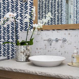 На фото: маленький туалет в морском стиле с фасадами в стиле шейкер, фасадами цвета дерева среднего тона, серой плиткой, настольной раковиной, столешницей из известняка, разноцветными стенами и плиткой мозаикой с