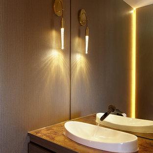 Cette photo montre un petit WC et toilettes tendance avec un lavabo posé, un placard à porte plane, un plan de toilette en cuivre, un WC suspendu et des portes de placard en bois sombre.