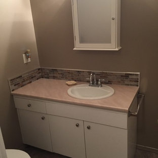Design ideas for a medium sized traditional cloakroom in Calgary with flat-panel cabinets, white cabinets, beige walls, slate flooring, a built-in sink and laminate worktops.