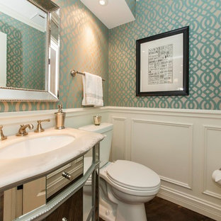 Small classic cloakroom in Chicago with a submerged sink, glass-front cabinets, grey cabinets, marble worktops, a two-piece toilet, multi-coloured walls and dark hardwood flooring.