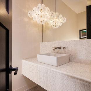 Klassische Gästetoilette mit beigefarbenen Fliesen, weißen Fliesen, Mosaikfliesen, beiger Wandfarbe, hellem Holzboden, Aufsatzwaschbecken, gefliestem Waschtisch und weißer Waschtischplatte in Sonstige